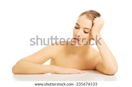 Close up of nude woman trying to take a nap at the desk. - stock photo
