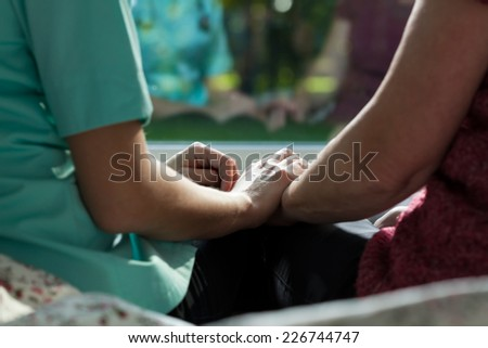 Close-up of nurse and woman sitting on the bed - stock photo