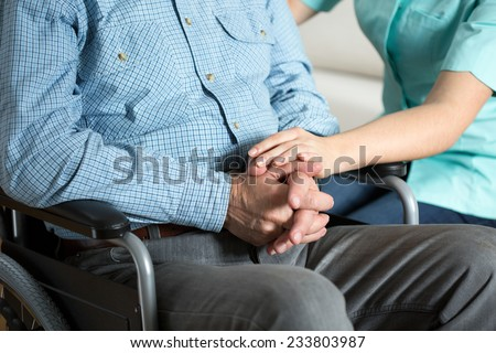 Close-up of nurse touching hand her handicapped patient - stock photo