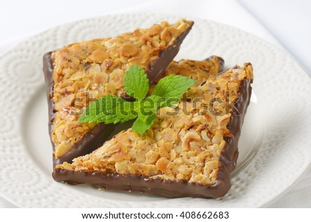 close up of nut triangular cookies on white plate - stock photo