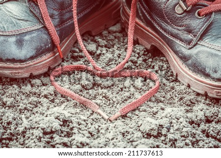 close up of old and dirty little baby booties on clay - heart shaped shoelace - stock photo