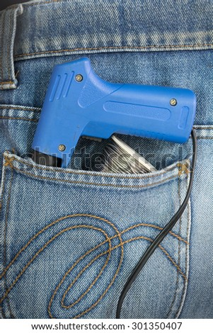 Close-up of old electric soldering iron gun with the blue handle and Roll of soldering wire in Blue Jeans Pocket. - stock photo