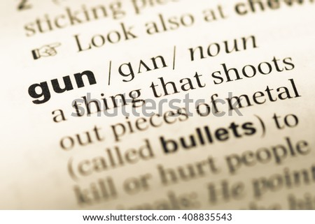 Close up of old English dictionary page with word gun - stock photo