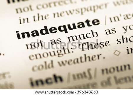 Close up of old English dictionary page with word inadequate - stock photo
