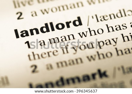 Close up of old English dictionary page with word landlord - stock photo
