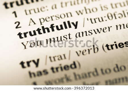 Close up of old English dictionary page with word truthfully - stock photo
