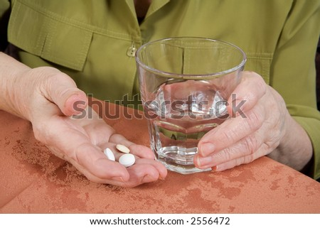 close up of old hands with tablets and a glass of water - stock photo