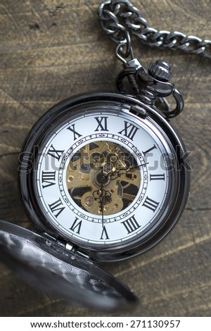 Close up of old pocket watch on rustic wooden background - stock photo