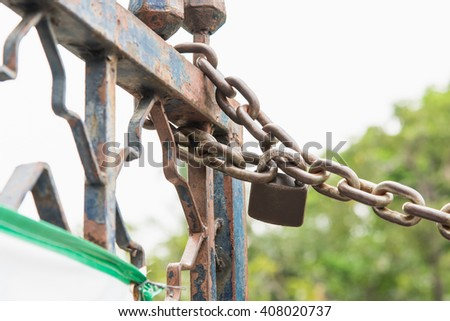 Close up of old rusty lock the chain on iron fence. - stock photo