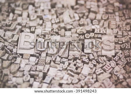 Close up of old used metal typeset letters with the word Business. Retro filter applied. - stock photo