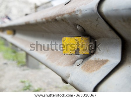 Close up of old yellow reflector on road - stock photo