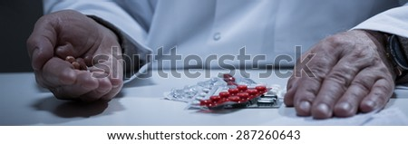 Close-up of older depressed man's handful of pills - stock photo