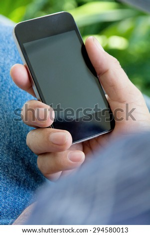 Close up of older man hand holding a smart phone - stock photo