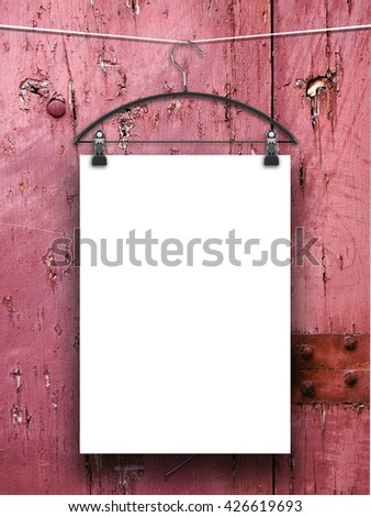 Close-up of one blank frame hanged by clothes hanger against pink weathered wooden boards background - stock photo