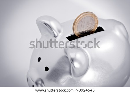 Close-up of one Euro coin partially inserted into the slot of a silver piggy bank. - stock photo