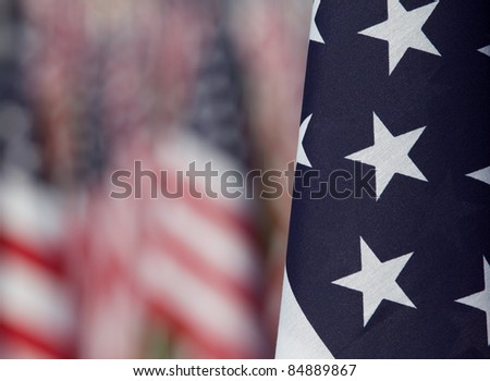 Close-up of  one flag with other flags purposely blurred in the background. Each flag was designed to represent a person who died in the terrorist attacks on 9/11/2001. - stock photo