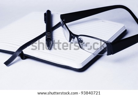 Close up of open diary topped with black pen and reading glasses isolated on gradient background - stock photo