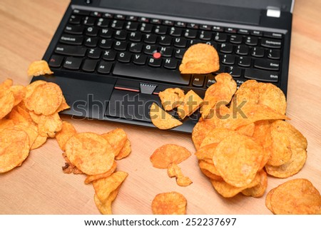 close up of open laptop with chips scattered on keyboard - stock photo - stock photo