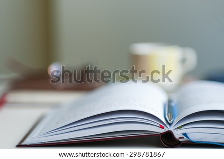 Close up of open notebook blurred with very shallow depth of field (soft focus)  - stock photo