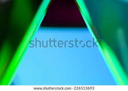 Close-up of optical glass prism and light reflection. blue and green reflection of a glass prism. - stock photo