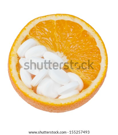Close up of orange and pills isolated - vitamin concept. - stock photo