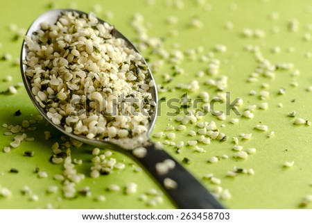 Close up of organic hemp seeds on silver spoon sitting on green background - stock photo