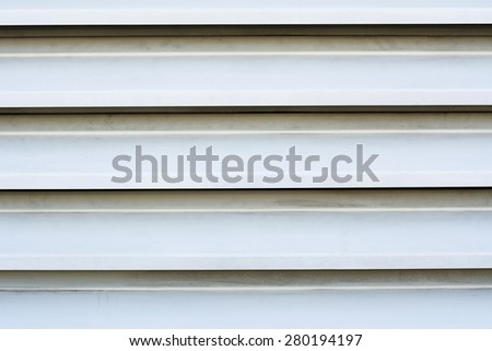 Close up of outdoor white louver vents on a seafood restaurant door circulating fishy aromas out of the restaurant. - stock photo