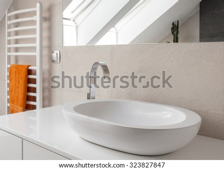 Close up of oval washbasin with new design silver tap - stock photo