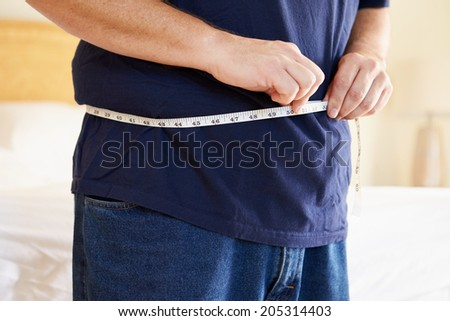 Close Up Of Overweight Man Measuring Waist - stock photo
