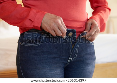 Close Up Of Overweight Woman Trying To Fasten Trousers - stock photo