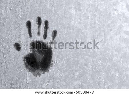 Close up of palm print on frozen winter window - stock photo