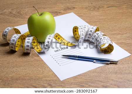 close up of paper with diet plan, apple and measure tape on wooden table - stock photo