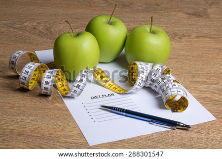 close up of paper with diet plan, green apples and measure tape on wooden table - stock photo