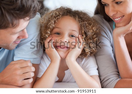 Close up of parents looking at their son while lying on a bed - stock photo
