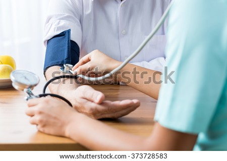 Close up of patient and doctor taking blood pressure - stock photo