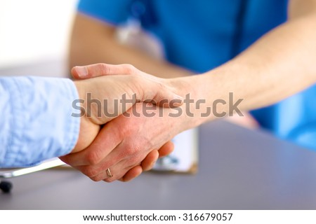 close up of patient and doctor taking notes - stock photo
