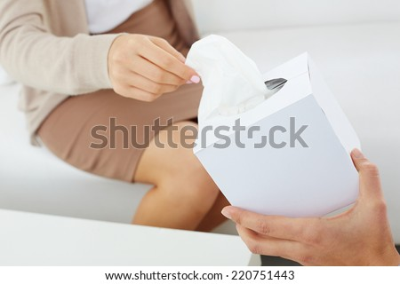 Close-up of patient hand taking paper tissue out of box being offered by her doctor - stock photo