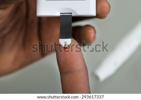 Close-up Of Patient Hands Measuring Glucose Level Blood Test With Glucometer - stock photo