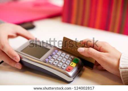 Close-up of payment through machine by plastic card - stock photo