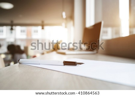 Close up of pen, withe paper and laptop at office sunny day vintage tone. - stock photo