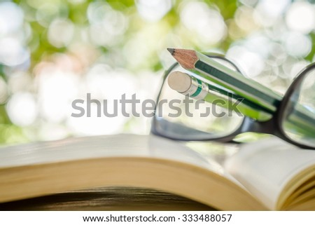 Close up of pencil , eyeglasses and open book on bokeh background, shallow deep of field on pencil and soft focus process - stock photo
