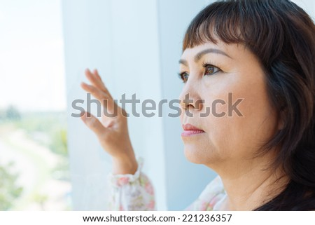 Close-up of pensive senior woman looking out of the window - stock photo