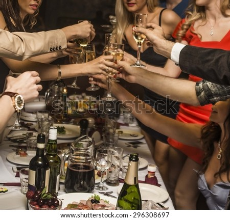 Close-up of people making good cheer Holiday Event people cheering each other with champagne and wine against the holiday table Empty space for inscription  - stock photo