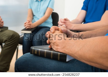 Close-up Of People Praying With Holy Bible - stock photo