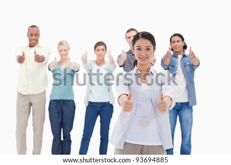 Close-up of people smiling with their thumbs-up against white background - stock photo