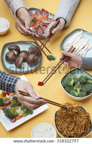 Close up of people using chopsticks with Chinese food - stock photo