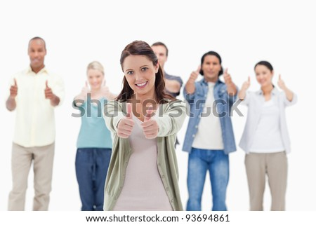 Close-up of people with their thumbs-up focus on the woman in foreground - stock photo