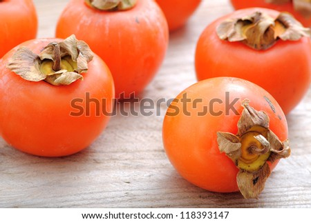 Close up of persimmon fruits. Fuyu, Persimmons fruits on white wood background.Winter holidays fruits. - stock photo