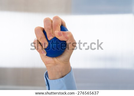 Close-up Of Person Hand Holding Blue Stressball - stock photo