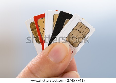 Close-up Of Person Hand Holding Four Phone Sim Cards - stock photo